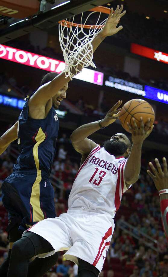 James Harden (13), who scored 33 in Saturday's win, lays one in under the Pelicans' Alexis Ajinca. Photo: Brett Coomer, Staff / © 2014 Houston Chronicle