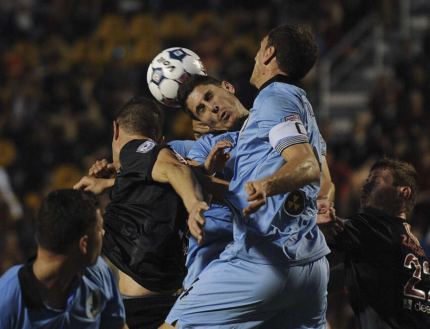Players from the Scorpions (black uniforms) and Minnesota United battle to control the ball off a corner kick during the season opener Saturday night at Toyota Field.