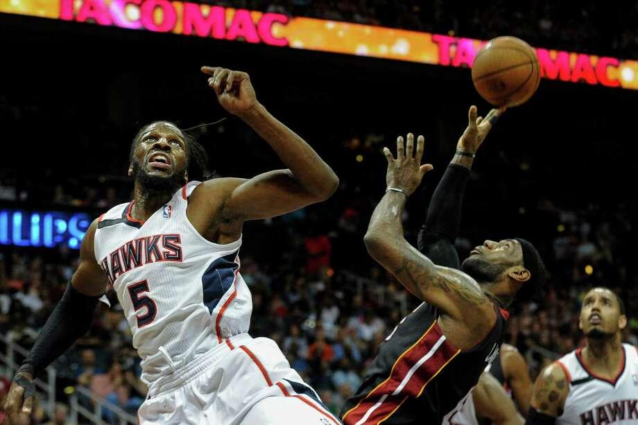 Miami Heat forward LeBron James, front right, is fouled under the basket by Atlanta Hawks forward DeMarre Carroll (5) during the first half of an NBA basketball game on Saturday, April 12, 2014, in Atlanta. (AP Photo/John Amis) ORG XMIT: GAJA102 Photo: John Amis / FR69715 AP