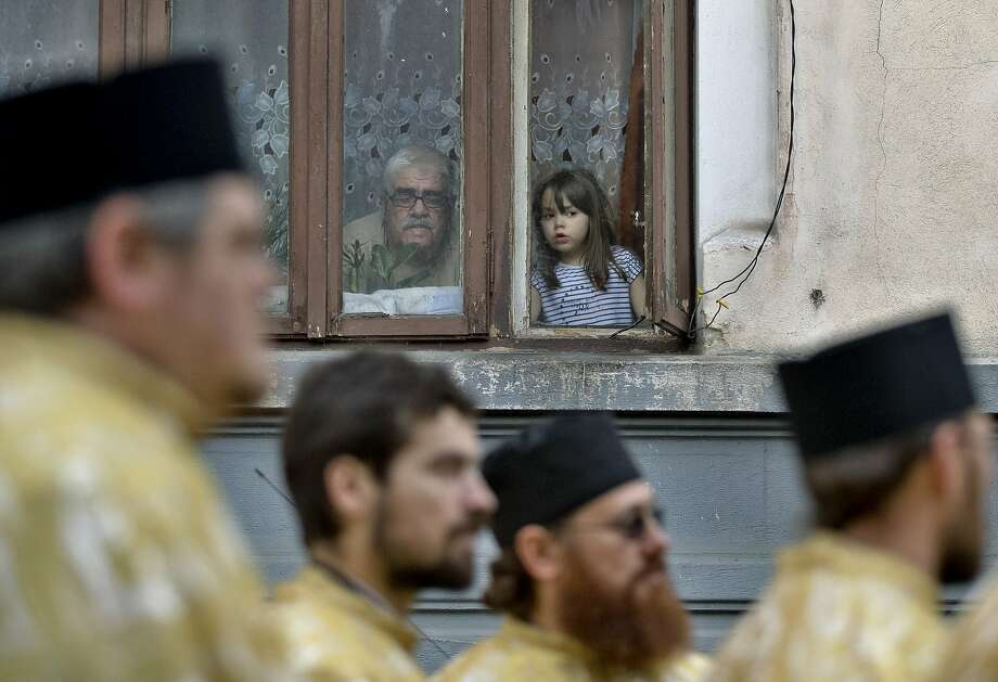 A child watches along with a man as Orthodox priests march before a Palm Sunday religious service back dropped by mural paintings in Bucharest, Romania, Saturday, April 12, 2014. According to local media 800 priests marched through the Romanian capital ahead of Palm Sunday. This year the country's Orthodox majority celebrates Easter along with the Catholics on April 20.(AP Photo/Vadim Ghirda) Photo: Vadim Ghirda, Associated Press