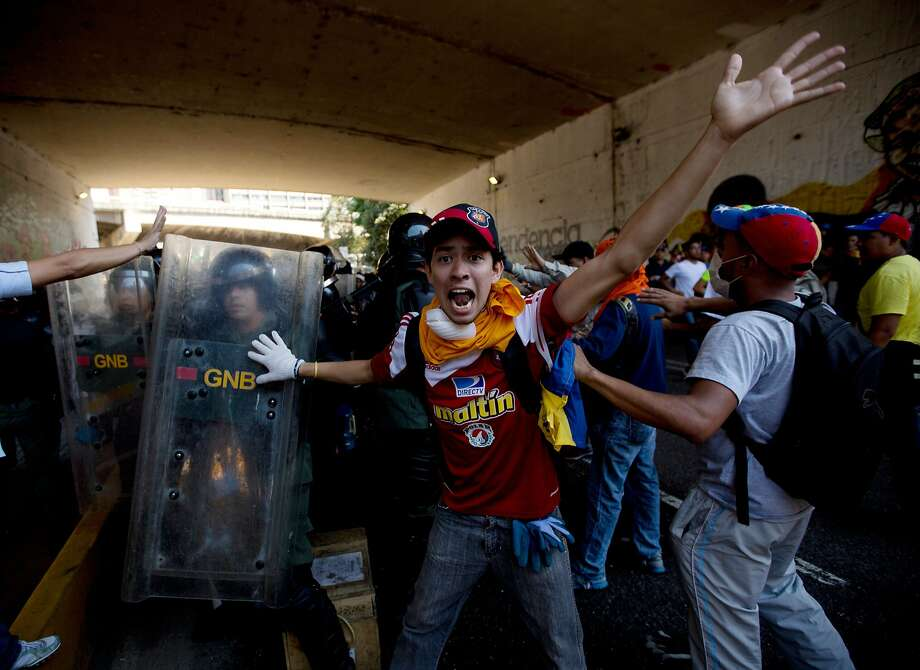 A university student protester shouts for fellow protesters to not attack the Bolivarian National Guards trapped under the highway with protesters on both sides during clashes in Caracas, Venezuela, Saturday, April 12, 2014. Students opposed to the government of President Nicolas Maduro are protesting after leaders of the opposition agreed this week to sit down with Maduro's government for talks aimed at defusing the nation's political crisis, now entering its third month. The two sides agreed that talks aimed at reconciliation would be held in public. (AP Photo/Fernando Llano) Photo: Fernando Llano, Associated Press