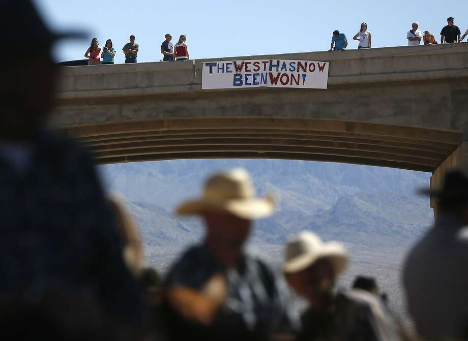 Protesters place a sign on a bridge near the Bureau of Land Management 's base camp where seized cattle, that belonged to rancher Cliven Bundy, are being held at near Bunkerville, Nevada April 12, 2014. U.S. officials ended a stand-off with hundreds of armed protesters in the Nevada desert on Saturday, calling off the government's roundup of cattle it said were illegally grazing on federal land and giving about 300 animals back to rancher Bundy who owned them. REUTERS/Jim Urquhart   (UNITED STATES - Tags: POLITICS ANIMALS BUSINESS CRIME LAW CIVIL UNREST) Photo: Jim Urquhart, Reuters