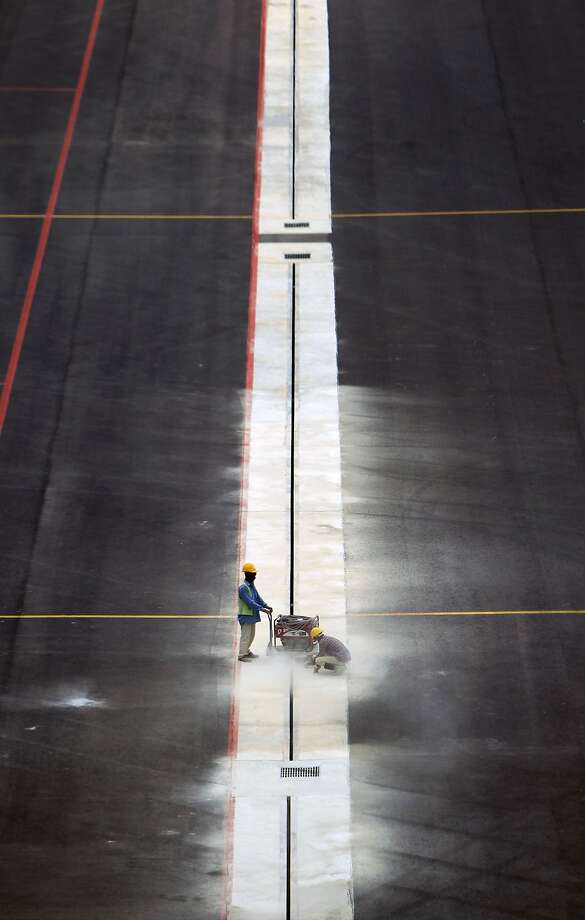 Workers line on the floor at the newly completed budget airport KLIA2, in Sepang, Malaysia, Saturday, April 12, 2014. The KLIA2 will start operating on May 2. (AP Photo/Lai Seng Sin) Photo: Lai Seng Sin, Associated Press