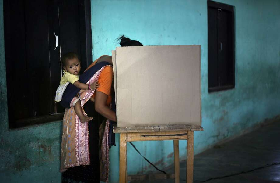 A Karbi woman in traditional attire carries her child on her back and casts her vote at a polling center in Diphu, in the northeastern Indian state of Assam, Saturday, April 12, 2014. The multiphase voting across the country runs until May 12, with results for the 543-seat lower house of parliament announced May 16. (AP Photo/Anupam Nath) Photo: Anupam Nath, Associated Press