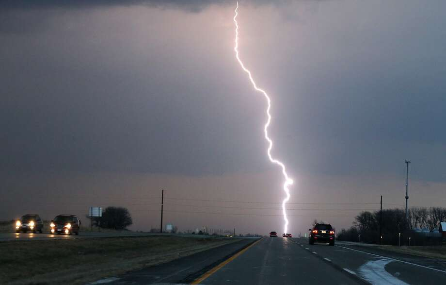 A bolt of lightning strikes along Interstate 35 north of Ames, Iowa, on Saturday, April 12, 2014, as a storm system passed through. (AP Photo/The Des Moines Register, Bryon Houlgrave) Photo: Bryon Houlgrave, Associated Press