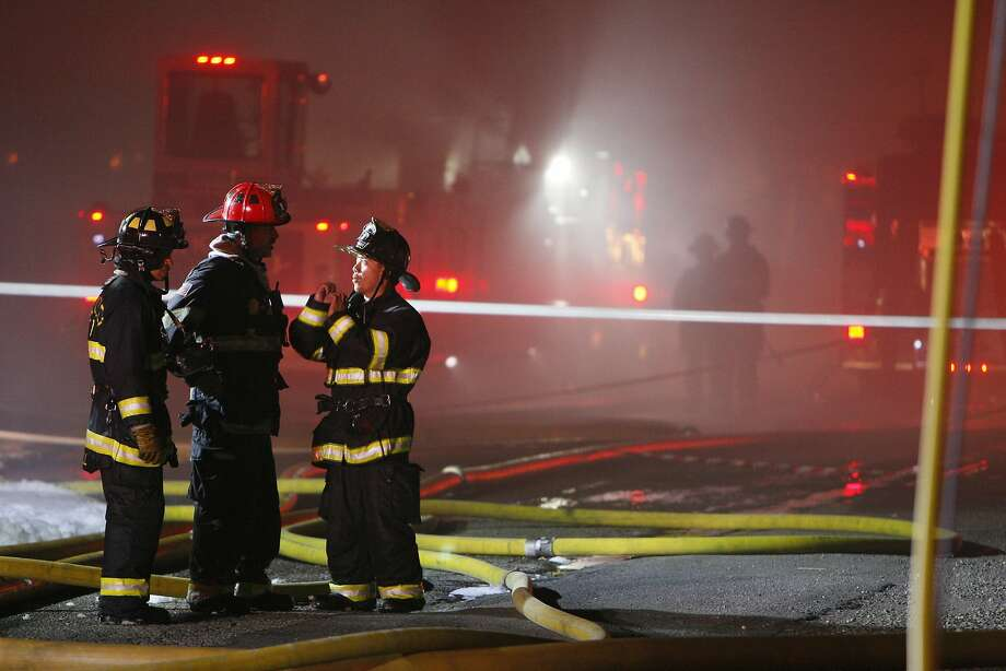 Firefighters talk to one another during a fire on the 1800 block of Second Street on April 12, 2014 in Berkeley, Calif. Photo: Codi Mills, The Chronicle