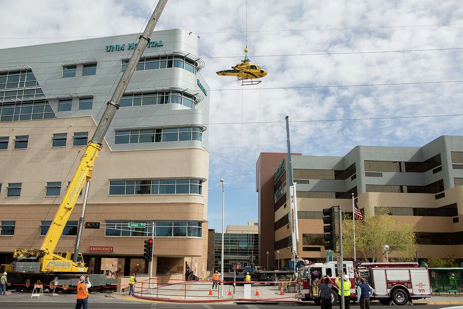 In this photo provided by the University of New Mexico Hospital, a medical helicopter is removed from the roof of University of New Mexico Hospital on Saturday, April 12, 2014 in Albuquerque, N.M.  UNM spokesman Billy Sparks says the hospital remained fully operational during the process. Sparks says the hospital temporarily converted to using power from an internal generator, eliminating the potential for any accidents ignited by outside power sources. Sparks says a tail section was the first piece removed followed by jet fuel, which was channeled into special hazmat barrels, and then the helicopter's body. Officials are hoping to begin construction repairs to the roof by Saturday night. The helicopter crashed on Wednesday. Photo: John Arnold, AP  / AP2014
