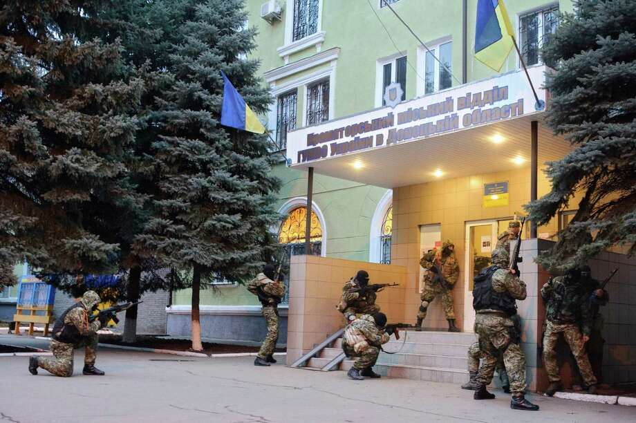 In this photo taken on Saturday, April  12, 2014, Armed pro-Russian activists occupy the police station in the eastern Ukraine town of Kramatorsk. The interior minister overnight reported an attack on a police in the city of Kramatorsk, close to the city of Slovyansk. A video from local news web-site Kramatorsk.info showed a group of camouflaged men armed with automatic weapons storming the building. The news web-site also reported that supporters of the separatist Donetsk People's Republic have occupied the administration building, built a barricade with tires around it and put a Russian flag nearby.  (AP Photo/Maxim Dondyuk, Russian Reporter magazine) Photo: Maxim Dondyuk, AP  / AP2014