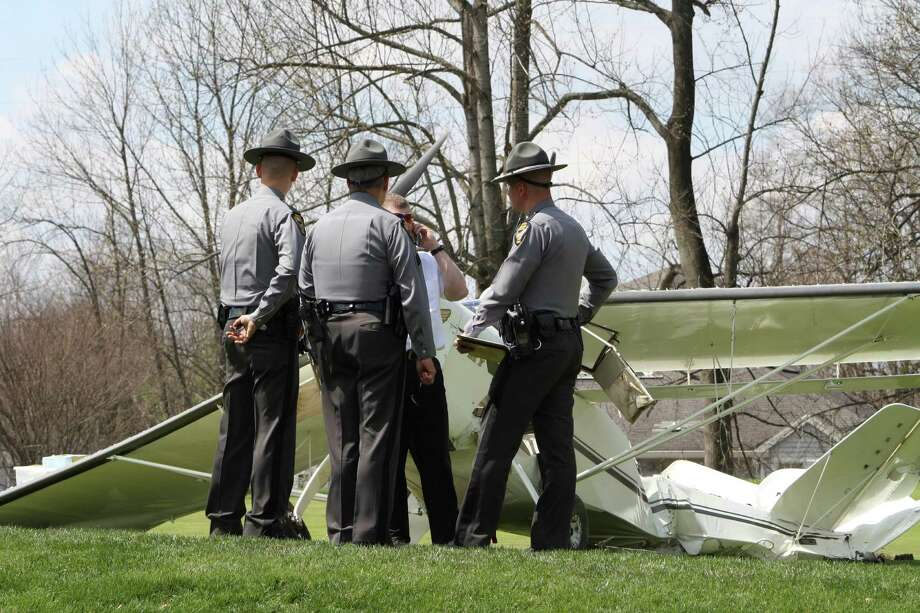 State Highway Patrol officers stand near a single-engine plane on the golf course of the Stillmeadow Country Club in Batavia, Ohio on Saturday, April 12, 2014 after an emergency landing. The State Highway Patrol says no injuries were reported. Photo: Adam Kiefaber, AP  / The Cincinnati Enquirer