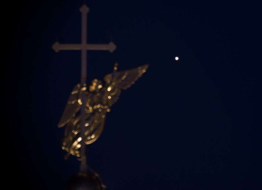 The planet Mars seen over a city landmark, a weather vane in the form of an angel, fixed atop a spire of the Saint Peter and Paul Cathedral in St.Petersburg, Russia, Friday, April 11, 2014. On April 8, 2014, Mars reached opposition in its nearly two-year orbit, when it's directly opposite the sun in our sky, and this year Mars will be closer to Earth than it has been since 2007, according to NASA. Photo: Dmitry Lovetsky, AP  / AP