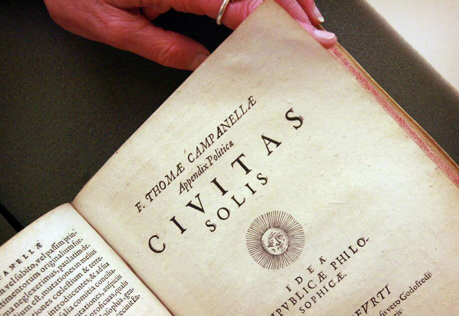 "This Wednesday, April 2, 2014 photo shows Melissa Conway, head of Special Collections & University Archives at University California Riverside, displays a rare first edition of utopian writer Tommaso Campanella's ""Civitas Solis"" (City of the Sun) book written in Latin. Conway  obtained a $54,000 grant from The Breslauer Foundation to purchase the book for the Eaton Collection of Science Fiction and Fantasy at UCR. (AP Photo/The Press-Enterprise, David Bauman) Photo: David Bauman, AP  / AP2014"