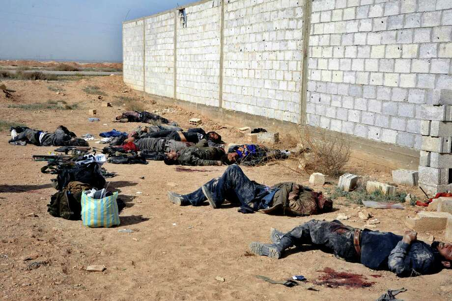 Thia photo released by the Syrian official news agency SANA, shows the dead bodies of Syrian rebels on the ground after they were killed by government forces, near Damascus, Syria, Monday, April 7, 2014. Syria's state-run media say several rebels were killed while they were rigging a car with explosives in the central city of Homs. Photo: Uncredited, AP  / AP2014