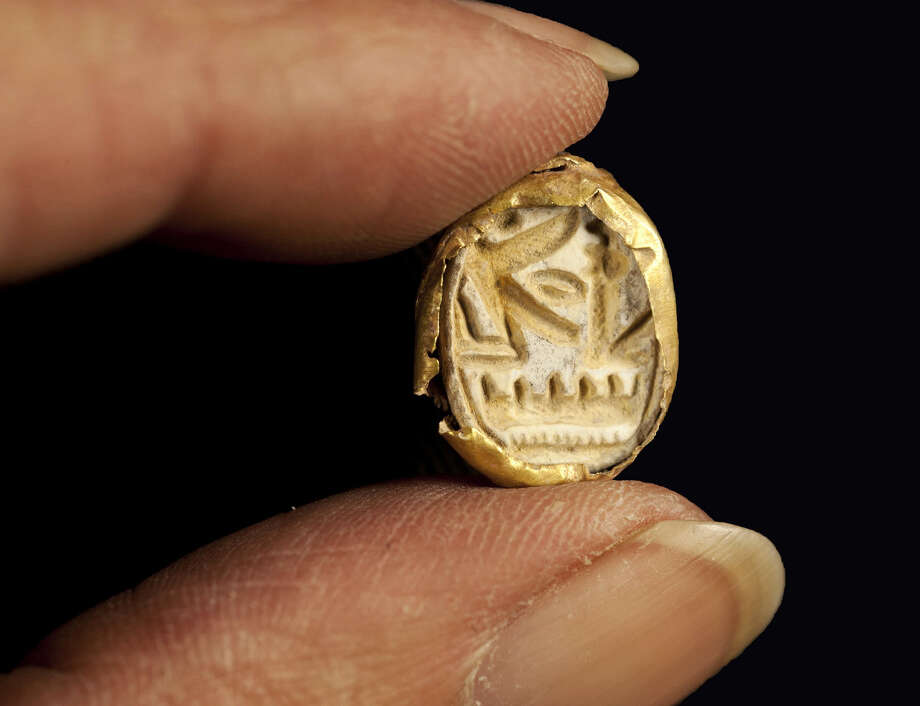 This undated photo released by Israel's Antiquities Authority shows a scarab seal ring encased in gold, carved with the name of Pharaoh Seti I, who ruled ancient Egypt in the 13th century BC, found at Tel Shadud, an archaeological mound in the Jezreel Valley. Israeli archaeologists have unearthed a rare sarcophagus featuring a slender face and a scarab ring inscribed with the name of an Egyptian pharaoh, Israel's Antiquities Authority said Wednesday April 9, 2014. Photo: Uncredited, AP  / AP2014