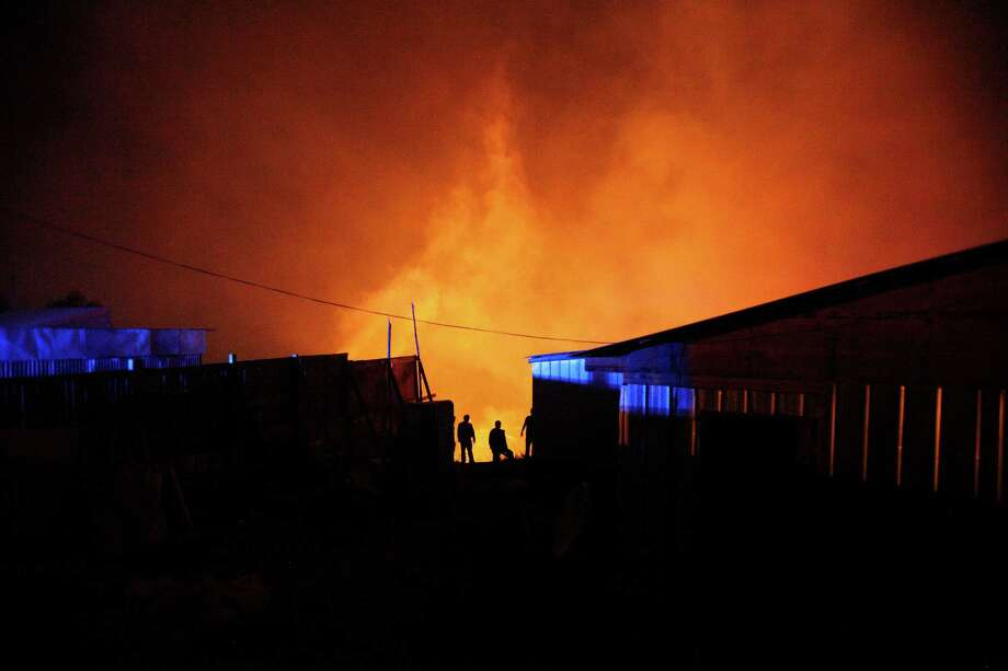 A group of firefighters stand next to burning homes as a forest fire rages towards urban areas in the city of Valparaiso, Chile, Sunday April 13, 2014. . Authorities say the fires have destroyed hundreds of homes, forced the evacuation of thousands and claimed the lives of at least seven people. Photo: Luis Hidalgo, AP  / AP2014