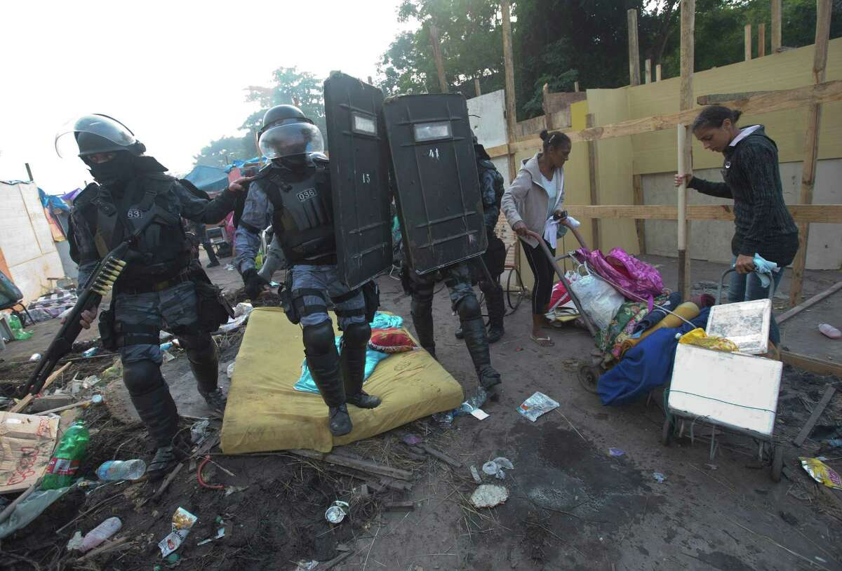 Women carry their belongings as policemen enter to an area occupied by squatters during an eviction in Rio de Janeiro, Brazil, Friday, April 11, 2014. Squatters in Rio de Janeiro are clashing with police after a Brazilian court ordered that 5,000 people be evicted from abandoned buildings of a telecommunications company. Officers have used tear gas and stun grenades to try to disperse the families.