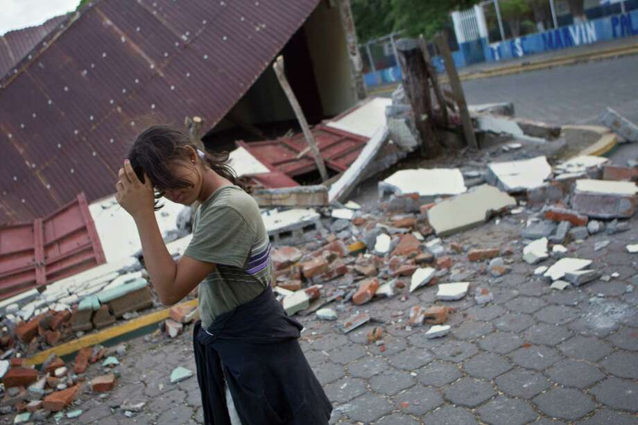 A girl walks in front a home damaged by an earthquake in Nagarote, Nicaragua, Friday, April 11, 2014. Nicaragua's President Daniel Ortega declared red alert Friday after an earthquake of 6.2 magnitude on the Richter scale that shook the country on Thursday and left one dead, hundreds of houses damaged and thousands of people affected . Photo: Esteban Felix, AP  / AP2014