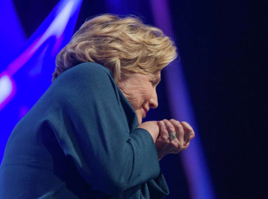 Former U.S. Secretary of State Hillary Rodham Clinton ducks as an object is thrown on stage during an address to members of the Institute of Scrap Recycling Industries during their annual convention at the Mandalay Bay Convention Center, Thursday, April 10, 2014, in Las Vegas. Clinton, a possible presidential contender in 2016, ducked but did not appear to be hit by the object, and then joked about the incident. Security ushered out a woman who said she threw a shoe but didn't identify herself to reporters or explain the action. (AP Photo/Las Vegas Sun, Steve Marcus) Photo: Steve Marcus, AP  / AP2014