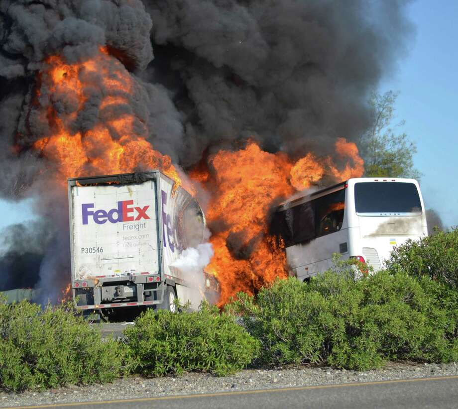 Massive flames engulf a tractor-trailer and a tour bus just after they collide on Interstate 5, Thursday, April, 10, 2014, near Orland, Calif. At least 10 people were killed in the crash, authorities said. Photo: Jeremy Lockett, AP  / THE ASSOCIATED PRESS2014