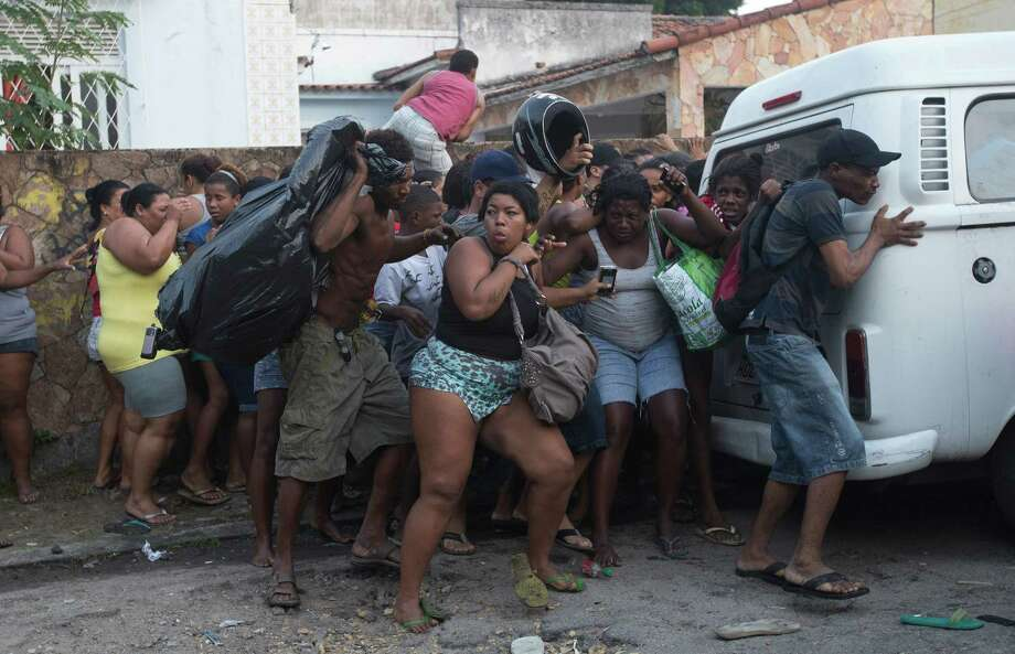 Squatters take cover from stun grenades and tear gas during an eviction in Rio de Janeiro, Brazil, Friday, April 11, 2014. Squatters in Rio de Janeiro are clashing with police after a Brazilian court ordered that 5,000 people be evicted from abandoned buildings of a telecommunications company. Officers have used tear gas and stun grenades to try to disperse the families. Photo: Silvia Izquierdo, AP  / AP2014