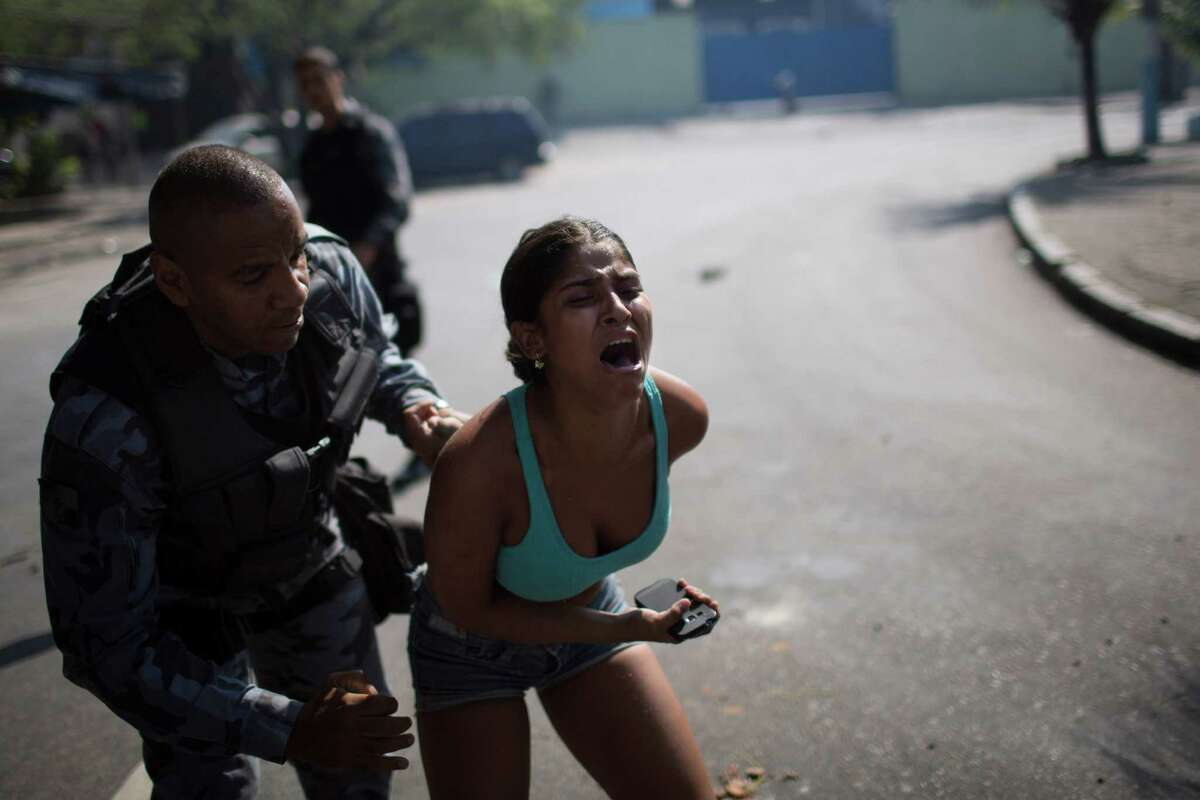 A woman screams while being detained during protests near the area recently occupied by squatters in Rio de Janeiro, Brazil, Friday, April 11, 2014. The woman was later released. Squatters in Rio de Janeiro are clashing with police after a Brazilian court ordered that 5,000 people be evicted from abandoned buildings of a telecommunications company. Officers have used tear gas and stun grenades to try to disperse the families.