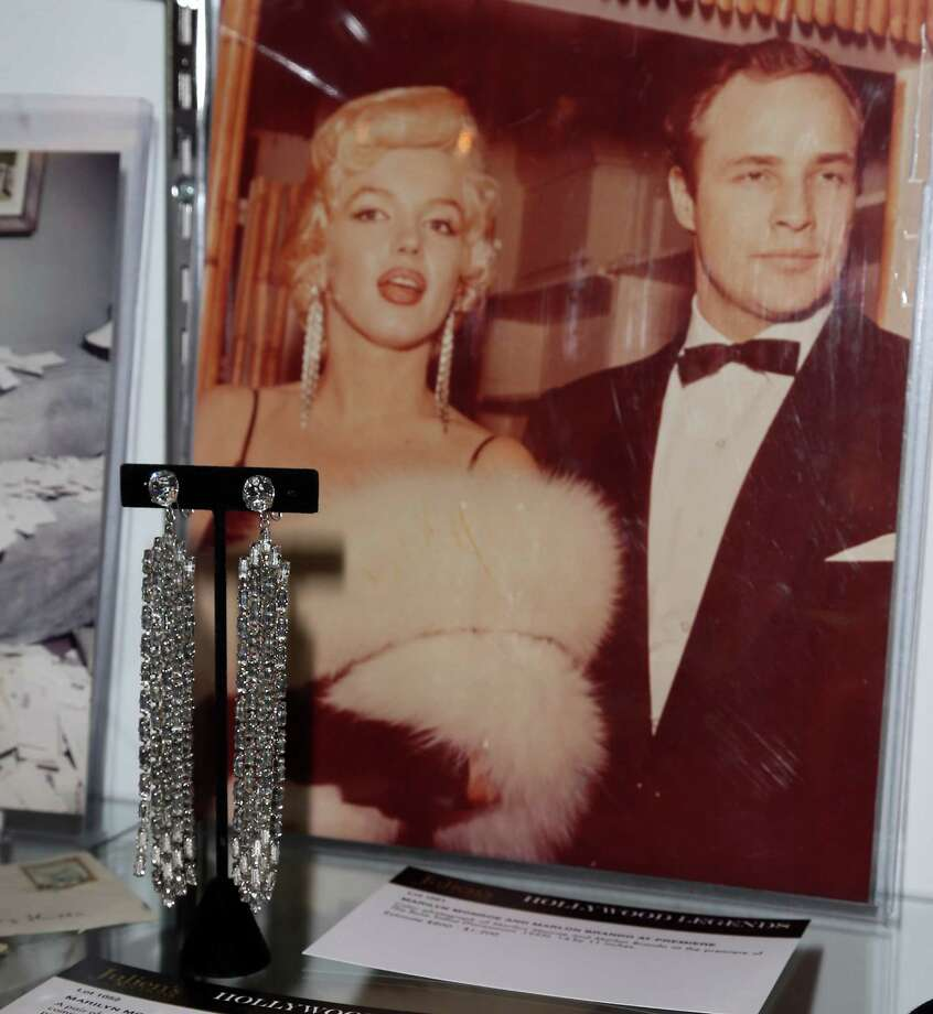 BEVERLY HILLS, CA - APRIL 07:  Marilyn Monroe earrings valued at between $150,000 to $200,000 in front of a photograph of Monroe (with Marlon Brando) wearing them are displayed at Julien's Auctions Hollywood Legends 2014 Press Preview Day at Julien's Auctions Gallery on April 7, 2014 in Beverly Hills, California. Photo: David Livingston, Getty Images / Getty Images