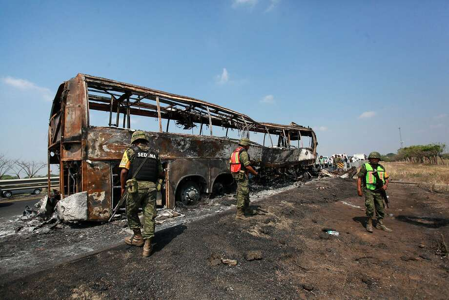 Soldiers guard the site where a passenger bus slammed into a broken-down truck and burst into flames near the town of Ciudad Isla in the Gulf state of Veracruz, Mexico, Sunday, April 13, 2014. Dozens of people traveling on the bus to Mexico City burned to death inside the bus. (AP Photo/Feliz Marquez) Photo: Felix Marquez, Associated Press