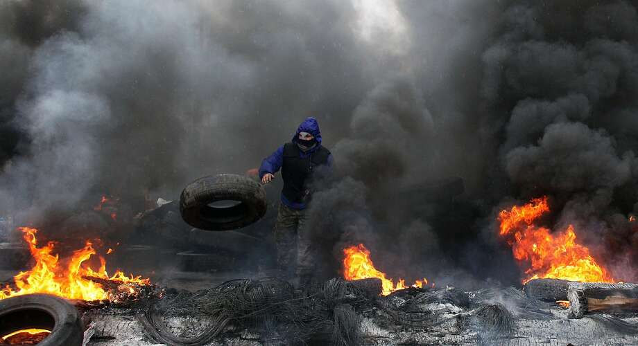 "A pro-Russian protester burns tires in prepararation for battle with the Berkut (Ukrainian special police forces) on the outskirts of the eastern Ukrainian city of Slavyansk on April 13, 2014. Ukraine on April 13 launched an ""anti-terrorist operation"" in the eastern town of Slavyansk, where pro-Russian gunmen have seized police and security services buildings, Interior Minister Arsen Avakov said. AFP PHOTO / ANATOLIY STEPANOVANATOLIY STEPANOV/AFP/Getty Images Photo: Anatoliy Stepanov, AFP/Getty Images"