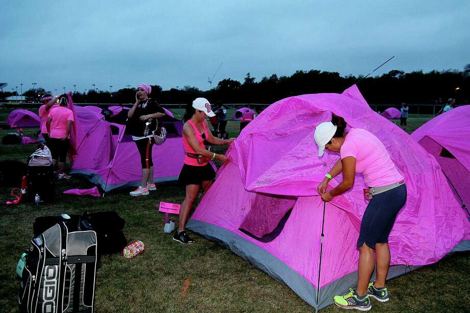 Jennifer Cox (77479) and Margie Torres (77494) breaking down thier tent. Walkers camped out in Pink Tents after the first leg of the Avon Walks for Breast Cancer Houston at the Avon Walk Wellness Village, Rice University. More than 1400 participants registered for this year's event. Photo by Pin Lim. Photo: Pin Lim, For The Chronicle / Copyright Pin Lim.