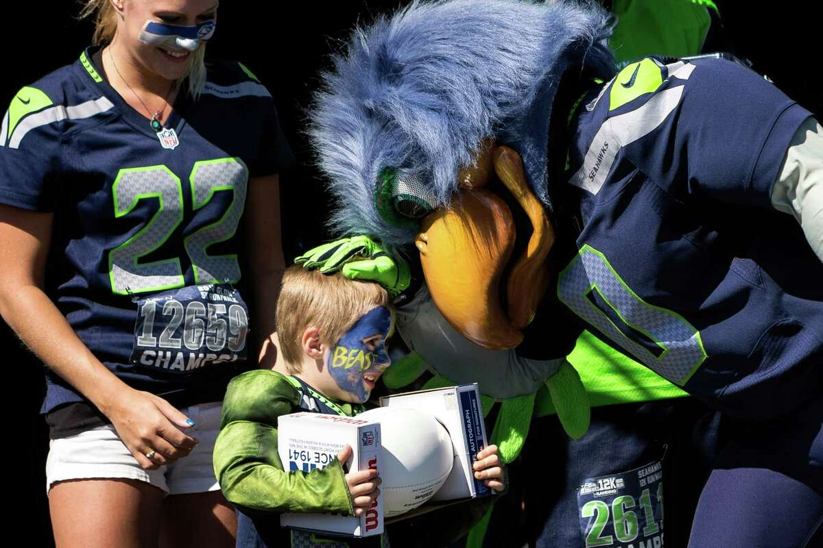 Seahawks mascot Blitz presents a young boy with a Russell Wilson signed football during a costume contest following the fifth annual Seahawks 12K Run Sunday, April 13, 2014, in Renton, Wash. The event featured three races: a 12 kilometer, five kilometer and children's run.