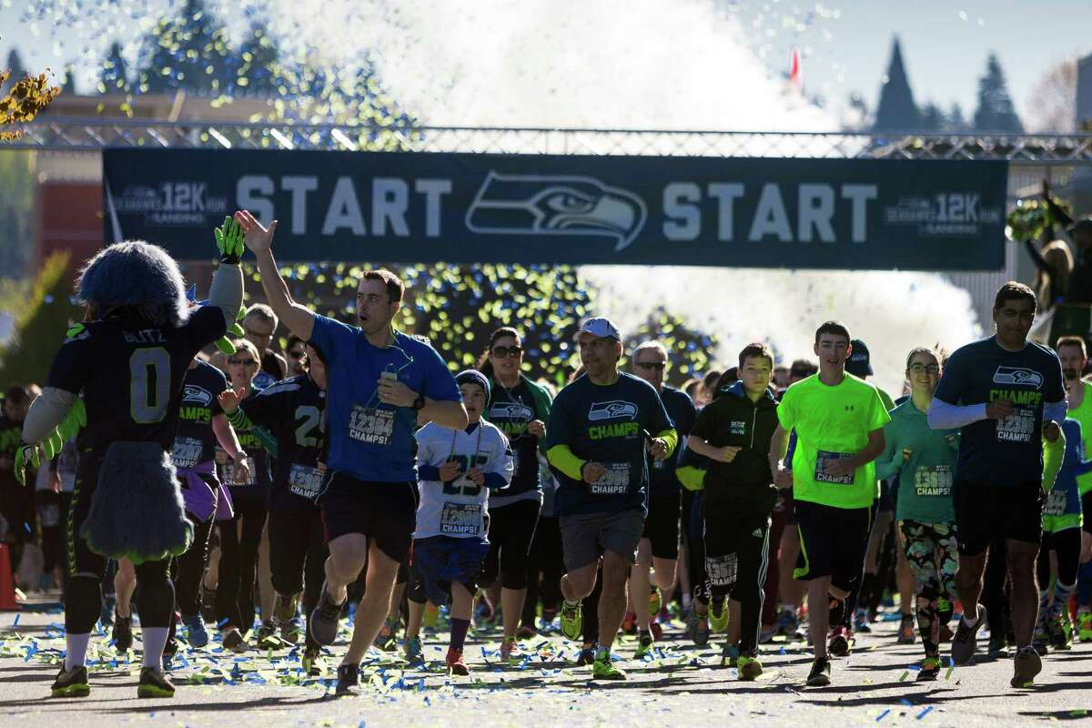 A runner high fives Blitz during the fifth annual Seahawks 12K Run Sunday, April 13, 2014, in Renton, Wash. The event featured three races: a 12 kilometer, five kilometer and children's run.