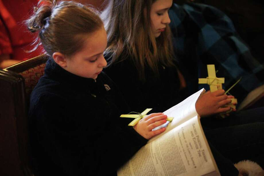 Justine Turcotte, 8, of Shelton follows the readings with her Palm cross during Palm Sunday service at St. Lawrence Parish in Huntington, Conn. On Sunday, April 13, 2014. Photo: BK Angeletti, B.K. Angeletti / Connecticut Post freelance B.K. Angeletti