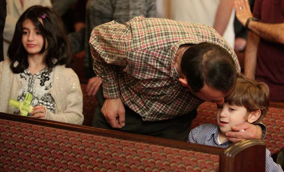 Tony Salluhi kisses his son, Mario, 5, during Palm Sunday service at St. Lawrence Parish in Huntington, Conn. On Sunday, April 13, 2014. Photo: BK Angeletti, B.K. Angeletti / Connecticut Post freelance B.K. Angeletti