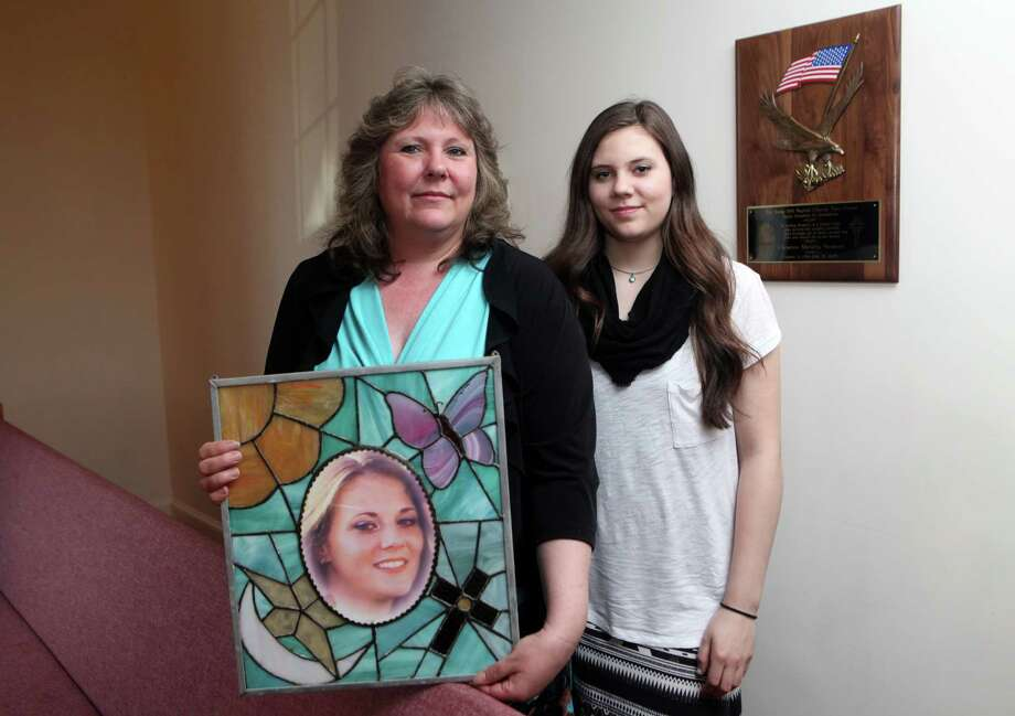 Maryjane Seymour holds a picture of her daughter, Cheyenne,  in the Long Hill Baptist church in Trumbull, where a plaque hangs in Cheyenne's honor. Cheyenne was serving in the military and died in car accident in 2005. With Maryjane is her daughter Kiowa, 16. A tree was recently planted in Cheyenne's honor in Twin Brooks Park in Trumbull. Sunday, April 14,  2014. Photo: BK Angeletti, B.K. Angeletti / Connecticut Post freelance B.K. Angeletti