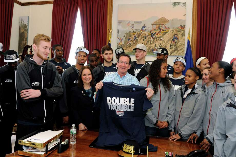 Connecticut Gov. Dannel P. Malloy holds a shirt in his office Sunday, April 13, 2014, in Hartford, Conn., as members of the UConn men's and women's basketball teams join him before a parade to honor their NCAA college basketball championships. AP Photo/Fred Beckham) Photo: Fred Beckham, AP / Associated Press