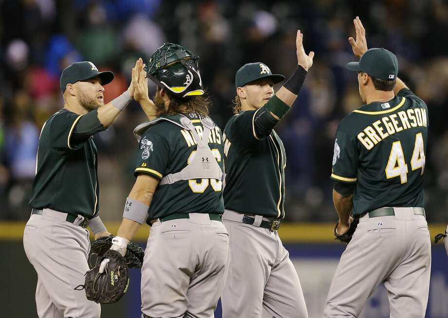 From left, Oakland Athletics' Daric Barton, Derek Norris, Josh Donaldson, and Luke Gregerson high-five after the A's defeated the Seattle Mariners 3-1 in a baseball game, Saturday, April 12, 2014, in Seattle. (AP Photo/Ted S. Warren) Photo: Ted S. Warren, Associated Press