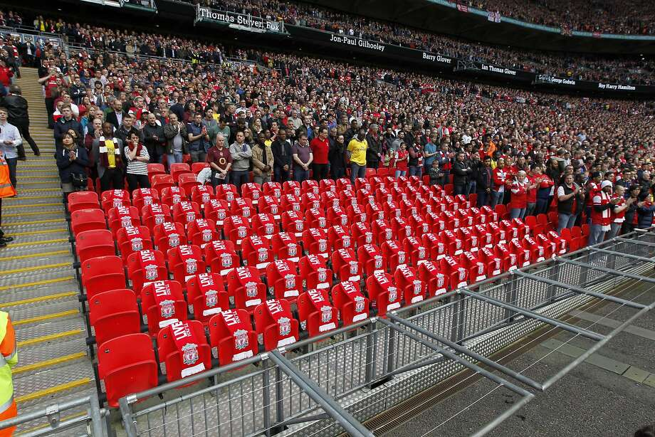 Fans at Liverpool hold a moment of silence for the 96 Liverpool supporters (symbolized by 96 empty seats) who died during a match 25 years ago. Photo: Ian Kington, AFP/Getty Images