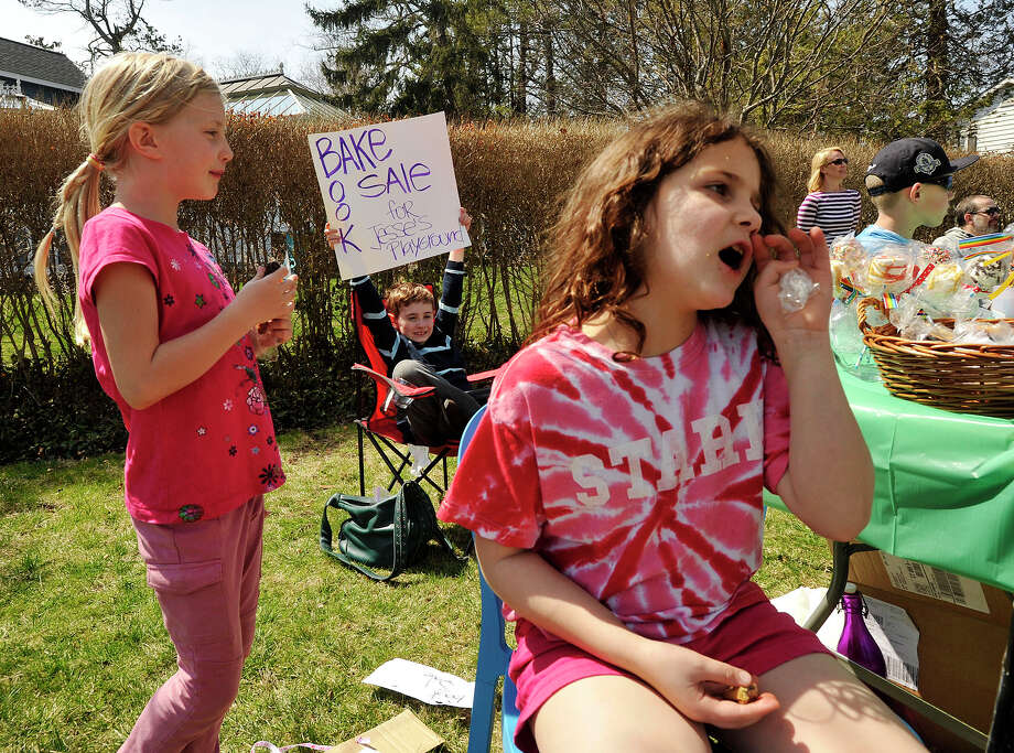 Emma Williams, left, Ryan O'Shea, center, and Alice Valerio try to get passing cars to stop while selling books, beverages and baked goods for the Sandy Ground: Where Angels Play charity along Shippan Avenue in Stamford, Conn., on Sunday, April 13, 2014. The charity is building playgrounds throughout New York, New Jersey and Connecticut with each playground commemorating one victim who died in the Sandy Hook Elementary School shooting. The group on Shippan Avenue is raising money for a playground on West Beach in Stamford in the memory of Jesse Lewis. There will be a fundraiser at Casey's Tavern on April 18. For more information, visit www.thesandygroundproject.org/. Photo: Jason Rearick / Stamford Advocate