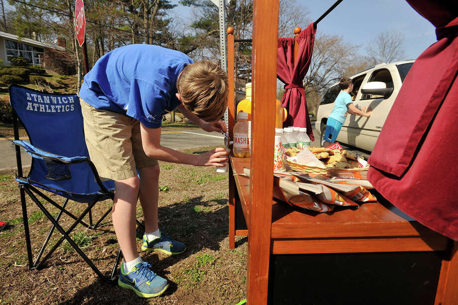 Grant, left, and Hayden Kuppenheimer sell lemonade, cookies and crackers across from Binney Park in Old Greenwich, Conn., on a warm Sunday, April 13, 2014. Photo: Jason Rearick / Stamford Advocate