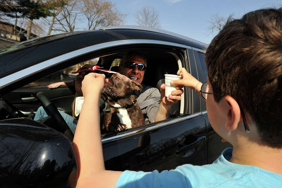Hayden Kuppenheimer, right, sells a glass of lemonade and a cookie to Peter Carino, as Peter's dog, Turtle, looks on across from Binney Park in Old Greenwich, Conn., on a warm Sunday, April 13, 2014. Photo: Jason Rearick / Stamford Advocate