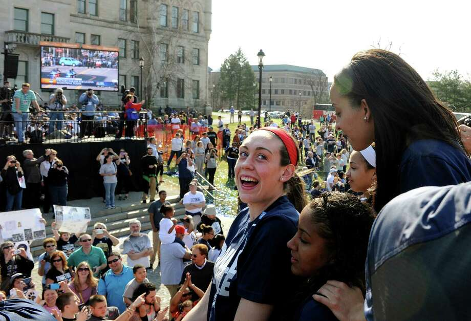 Connecticut's Breanna Stewart, center, looks back at Bria Hartley, top right, and Kaleena Mosqueda-Lewis, bottom, during a parade celebrating their team's NCAA women's college basketball championship, in Hartford, Conn., on Sunday, April 13, 2014. Photo: Fred Beckham, AP / Associated Press