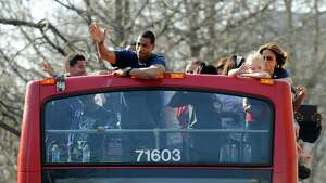 Connecticut men's basketball coach Kevin Ollie waves to a crowd during a parade in Hartford, Conn., on Sunday, April 13, 2014, celebrating UConn's wins in the NCAA men's and women's tournaments earlier this month.