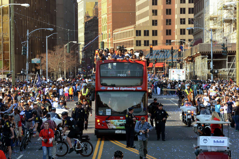 The UConn men's basketball team rides in an open air bus through the streets in a UConn Victory Parade  and Rally held for them and the women's team in downtown Hartford, Conn. on Sunday April 13, 2014. Photo: Christian Abraham / Connecticut Post