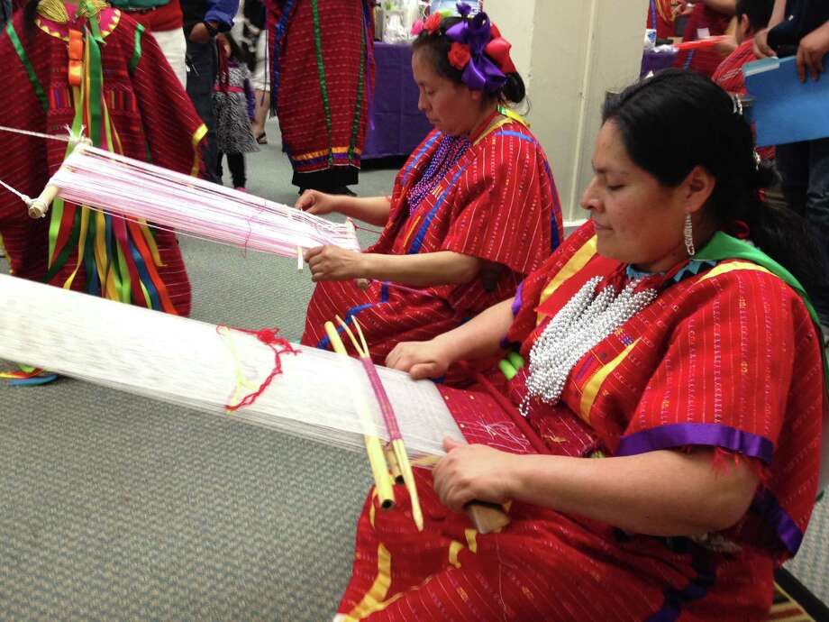 Two members of the local Triqui community demonstrate the use of a traditional backstrap loom at the April 12, 2014 first Day of Triqui Culture in the Capital Region at the University at Albany. (Photo courtesy of George Aaron Broadwell)