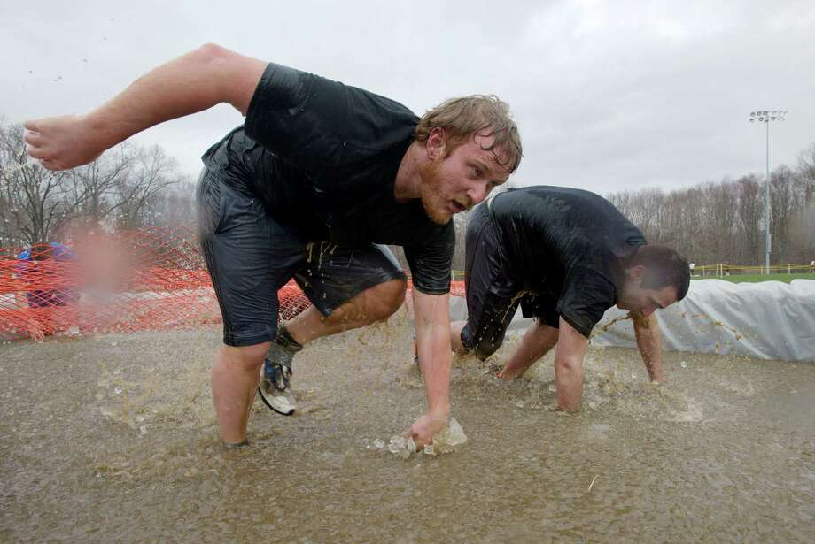 "Andy Rumore, 21, of Norwalk, left, and Matt Esmaieli, 21, of Woodstock, climb out of an ice bath during the ""Chuck's Mini-Mudder"" held at Western Connecticut State University, in Danbury, Conn, on Sunday, April 13, 2014. Rumore and Esmaieli are room mates and WCSU marketing majors. Photo: H John Voorhees III / The News-Times Freelance"