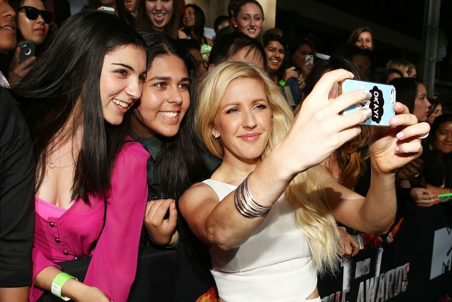 Recording artist Ellie Goulding (R) poses for a selfie with fans at the 2014 MTV Movie Awards at Nokia Theatre L.A. Live on April 13, 2014 in Los Angeles, California.  (Photo by Christopher Polk/Getty Images for MTV) Photo: Christopher Polk, Getty Images For MTV