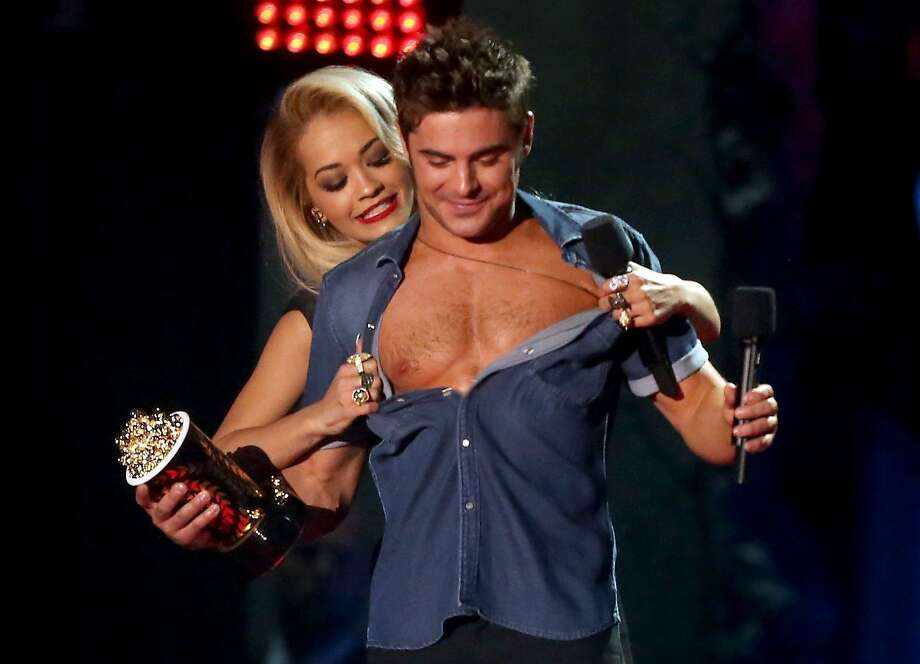 Actor Zac Efron (R) accepts the Best Shirtless Performance award for 'That Awkward Moment' from singer Rita Ora (L) onstage at the 2014 MTV Movie Awards at Nokia Theatre L.A. Live on April 13, 2014 in Los Angeles, California. Photo: Frederick M. Brown, Getty Images
