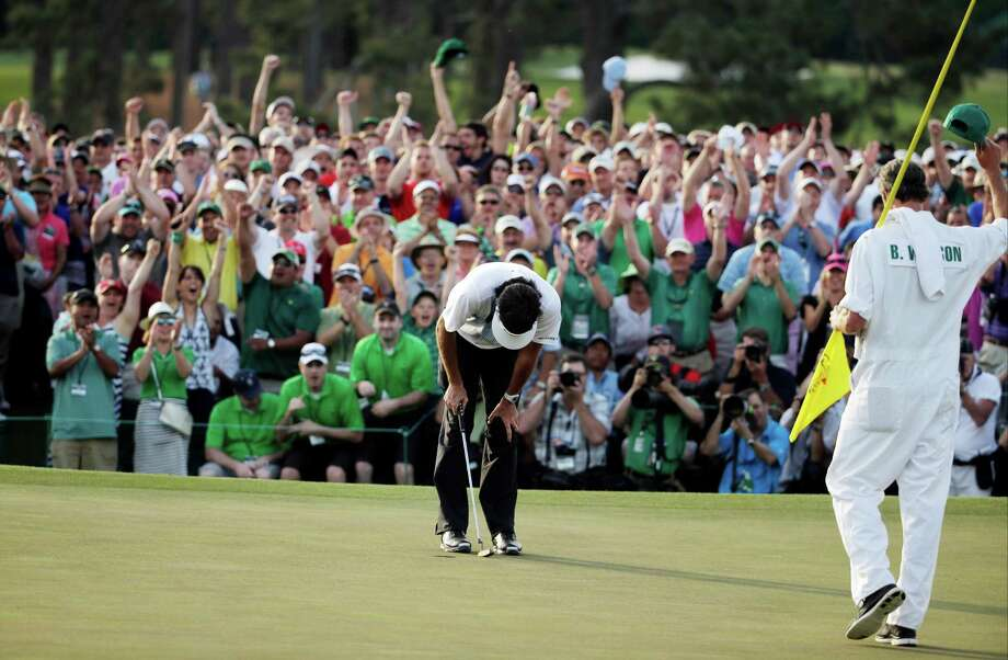Bubba Watson's caddie Ted Scott, right and spectators celebrate as Bubba Watson wins the Masters golf tournament Sunday, April 13, 2014, in Augusta, Ga. (AP Photo/Chris Carlson)  ORG XMIT: AUG248 Photo: Chris Carlson / AP