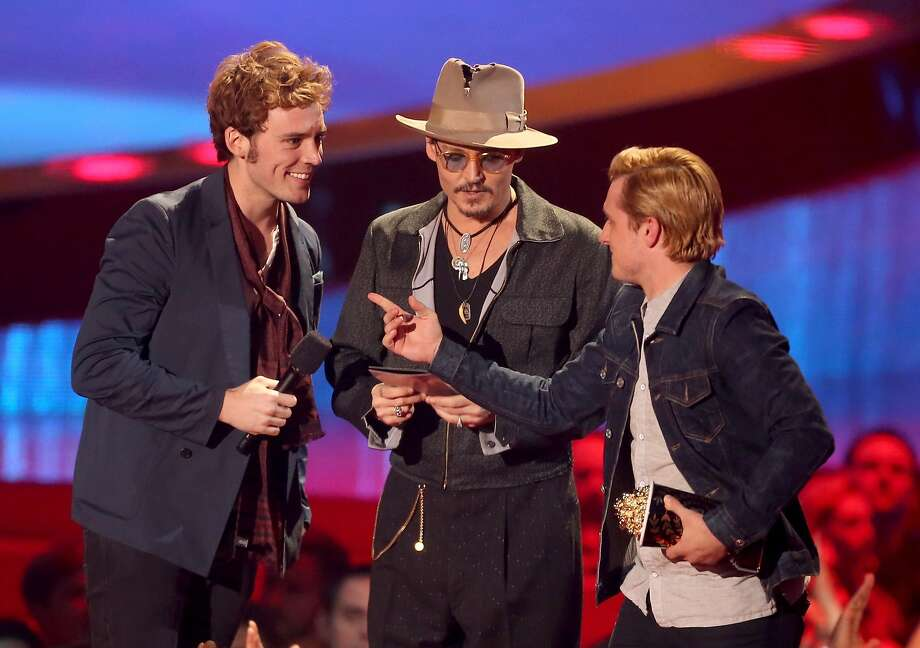 LOS ANGELES, CA - APRIL 13:  Actors Sam Claflin (L) and Josh Hutcherson (R) accept the Movie of the Year award for 'The Hunger Games: Catching Fire' from actor Johnny Depp (C) onstage at the 2014 MTV Movie Awards at Nokia Theatre L.A. Live on April 13, 2014 in Los Angeles, California.  (Photo by Frederick M. Brown/Getty Images) Photo: Frederick M. Brown, Getty Images