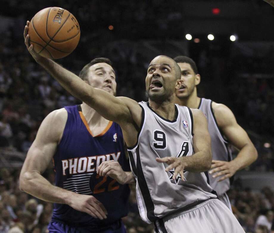 Tony Parker, driving on Phoenix's Miles Plumlee in Friday's 112-104 win, scored 14 of his 18 points in the third quarter. Photo: Kin Man Hui / San Antonio Express-News / ©2014 San Antonio Express-News