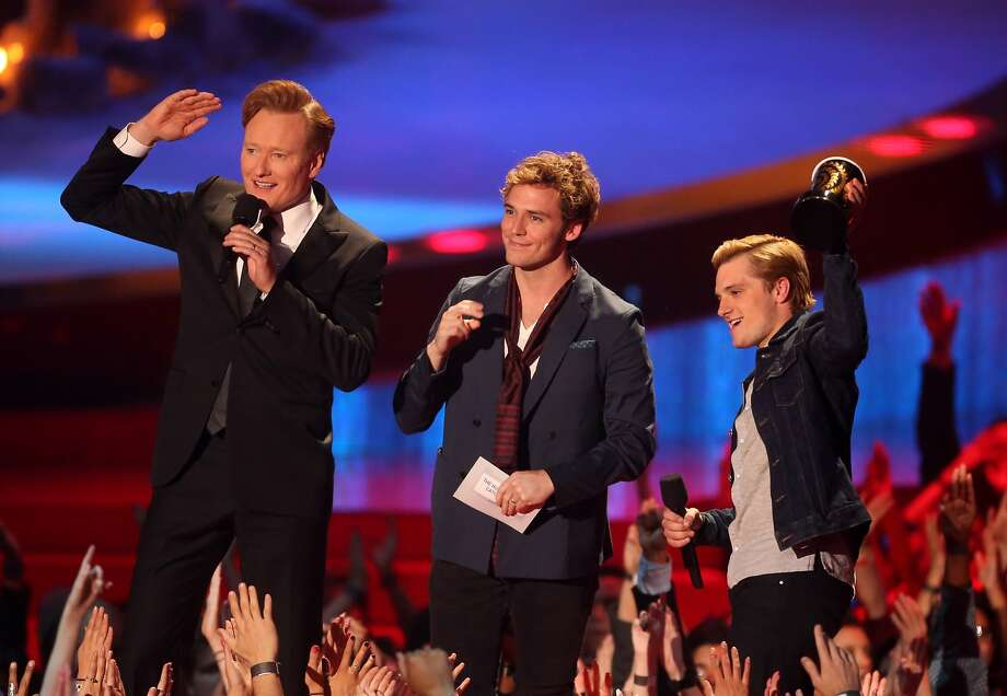 (L-R) Host Conan O'Brien with actors Sam Claflin and Josh Hutcherson, winners of the Movie of the Year award for 'The Hunger Games: Catching Fire,' speak onstage at the 2014 MTV Movie Awards at Nokia Theatre L.A. Live on April 13, 2014 in Los Angeles, California. Photo: Frederick M. Brown, Getty Images